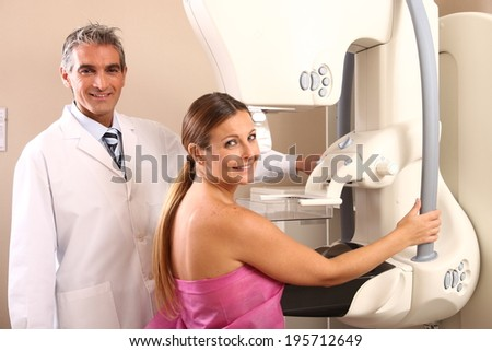 Happy male caucasian doctor assisting a woman patient at mammography machine. - stock photo
