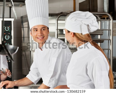 Happy male chef looking at female colleague at commercial kitchen - stock photo
