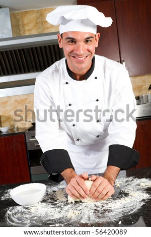 happy male chef making dough in kitchen