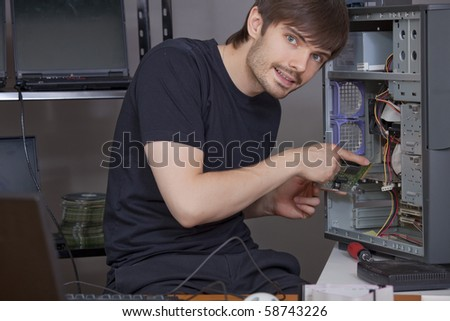 happy male computer technician installing new hardware - stock photo