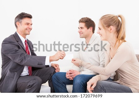 Happy Male Consultant Giving Visiting Card To Young Couple - stock photo