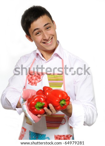 Happy male cook in apron with red peppers - stock photo