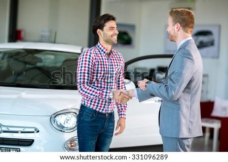 Happy male customer handshake with car dealer - stock photo