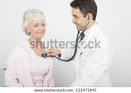 Happy male doctor checking patient using stethoscope