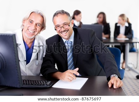 Happy male doctor discussing with patient at his clinic - colleagues in the background - stock photo