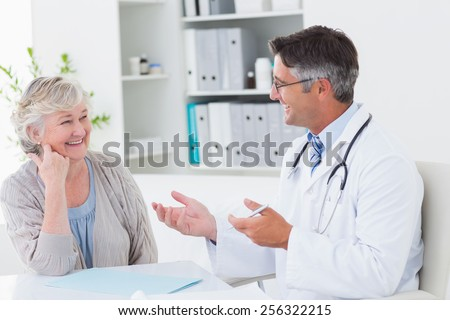 Happy male doctor discussing with senior patient at table in clinic - stock photo