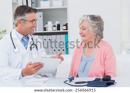 Happy male doctor explaining prescriptions to senior patient in clinic - stock photo