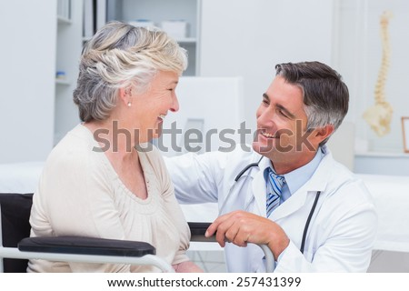 Happy male doctor looking at female patient in clinic - stock photo