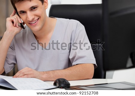 Happy male doctor talking on mobile phone at his desk - stock photo