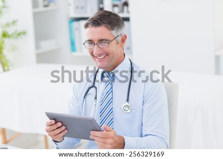 Happy male doctor using tablet computer in clinic
