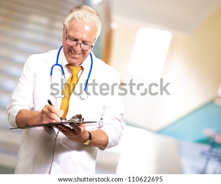 Happy Male Doctor Writing On Clipboard, Indoor - stock photo