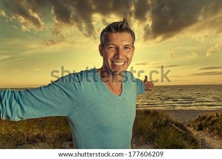 happy male embracing the world with wonderful landscape - stock photo