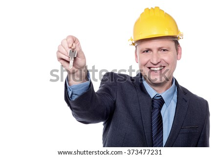Happy male engineer giving new house key - stock photo