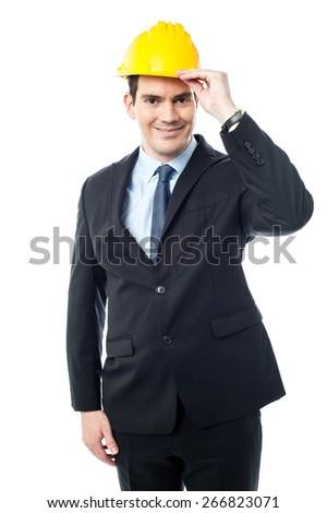 Happy male engineer posing with yellow hardhat - stock photo