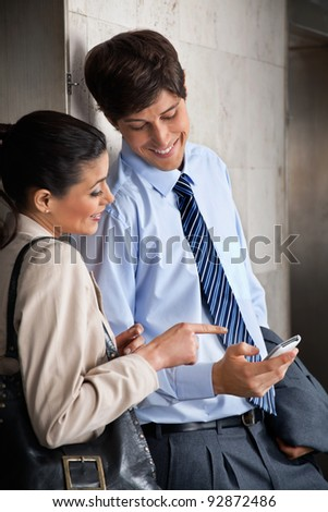 Happy male executive sharing text message on mobile phone with female colleague - stock photo