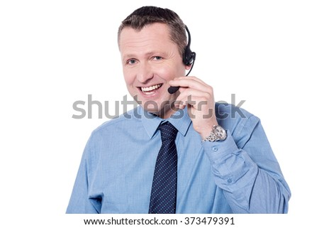 Happy male executive talking with customer using headphone