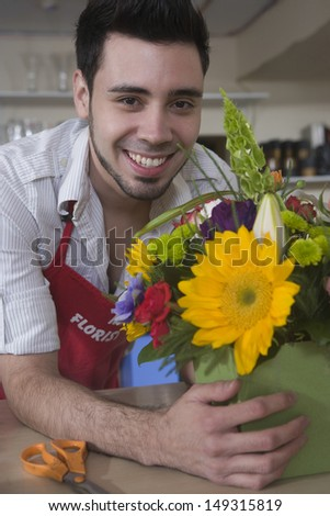 Happy male florist with flowers leaning on counter at shop - stock photo
