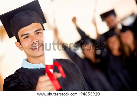 Happy male graduate holding his diploma and smiling - stock photo