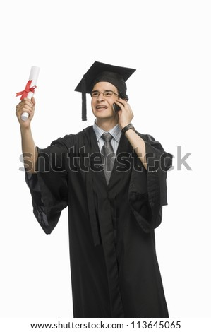 Happy male graduate holding his diploma and talking on a mobile phone
