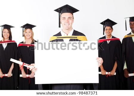 happy male graduate holding white board - stock photo