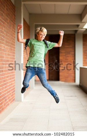 happy male high school student jumping up in school - stock photo