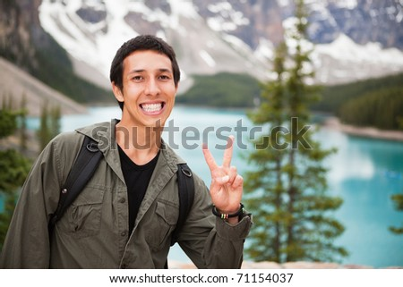 Happy male hiker showing you the victory sign against natural background - stock photo