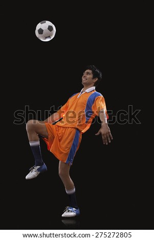 Happy male Indian soccer player doing kick ups isolated over black background - stock photo