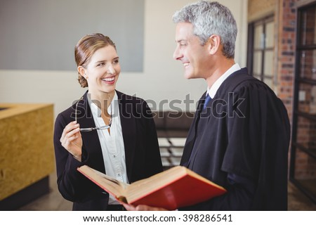 Happy male lawyer with book standing by female colleague at office - stock photo