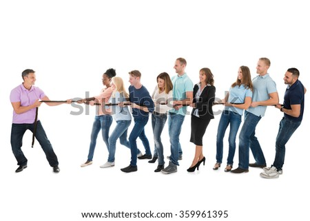 Happy male leader pulling creative business team while playing tug of war against white background - stock photo