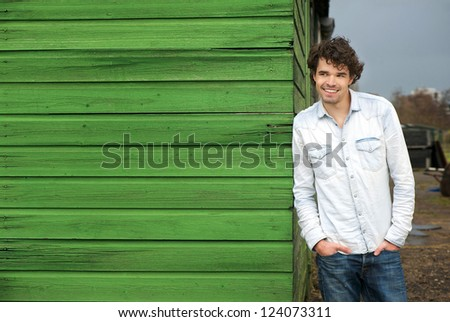 Happy male model leaning against green wooden wall outdoor. Hands in pockets and smile expression on his face - stock photo