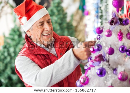 Happy male owner in Santa hat decorating Christmas tree at store - stock photo