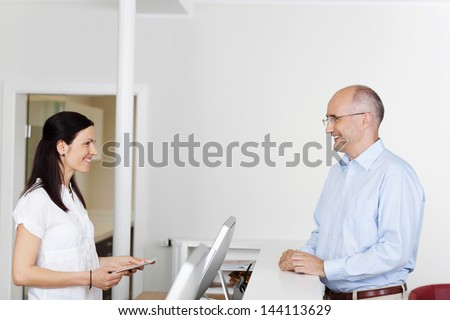Happy male patient and receptionist looking at each other - stock photo