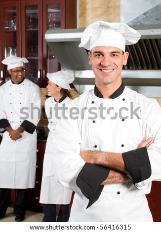 happy male professional chefs in industrial kitchen with colleagues behind