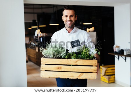 Happy male restaurant manager standing with box full of fresh spices - stock photo