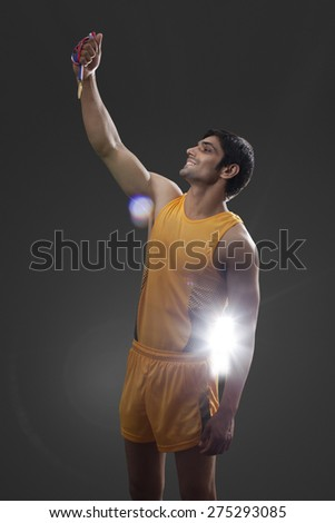 Happy male runner holding gold medal isolated over black background - stock photo