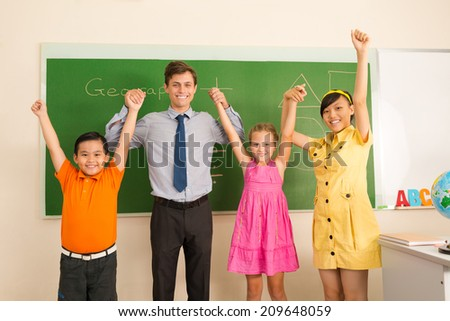 Happy male school teacher and his pupils posing in the classroom - stock photo