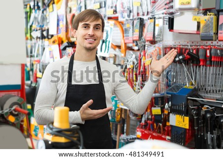 happy male seller posing at tooling section of household store