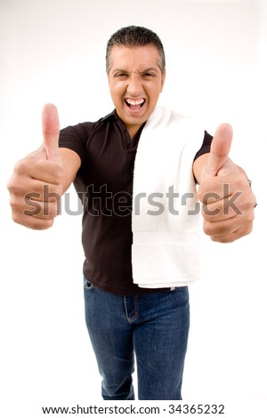Happy male showing thumbs up with towel on shoulders - stock photo
