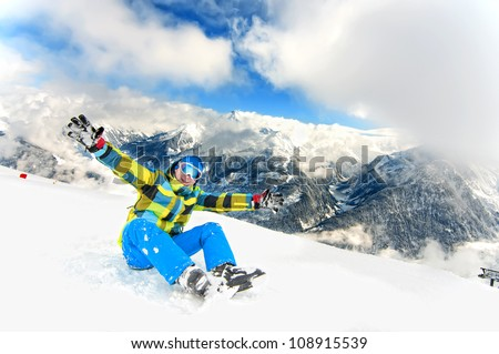 happy male sitting on slope, resting after skiing and gesturing with his hands - stock photo