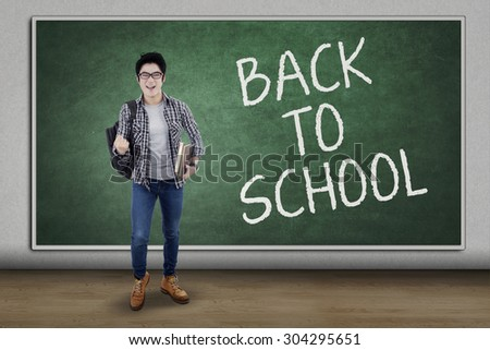Happy male student celebrate back to school in the classroom while carrying backpack and books - stock photo