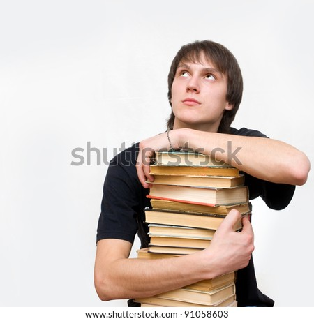 Happy male student holding a stack of books and dreams of a white background
