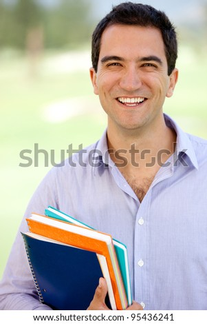 Happy male student holding notebooks outdoors looking casual