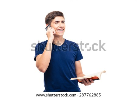 Happy male student talking on the phone and holding book isolated on a white background - stock photo