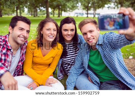 Happy male taking picture with his college friends in the park