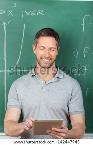 Happy male teacher using digital tablet against chalkboard in classroom - stock photo