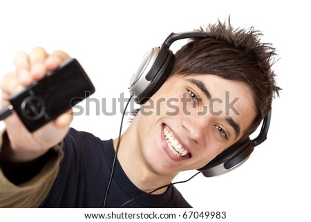 Happy male Teenager with headphones shows mp3 music player. Isolated on white background.