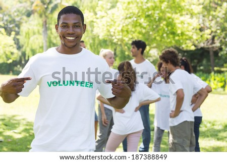 Happy male volunteer pointing at tshirt with friends in background