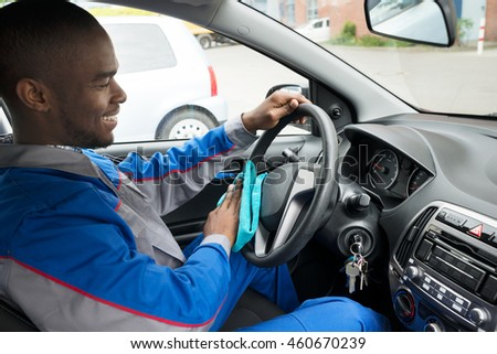 Happy Male Worker Cleaning Steering Wheel Of Car With Blue Cloth