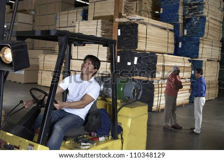 Happy male worker driving fork truck in warehouse - stock photo
