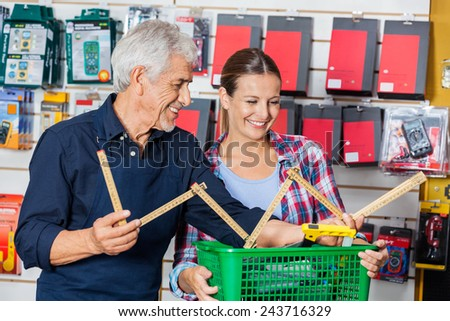 Happy male worker showing folding ruler to customer in hardware shop - stock photo